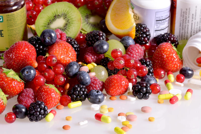 Berries, fruits, vitamins and nutritional supplements. On a white background royalty free stock images