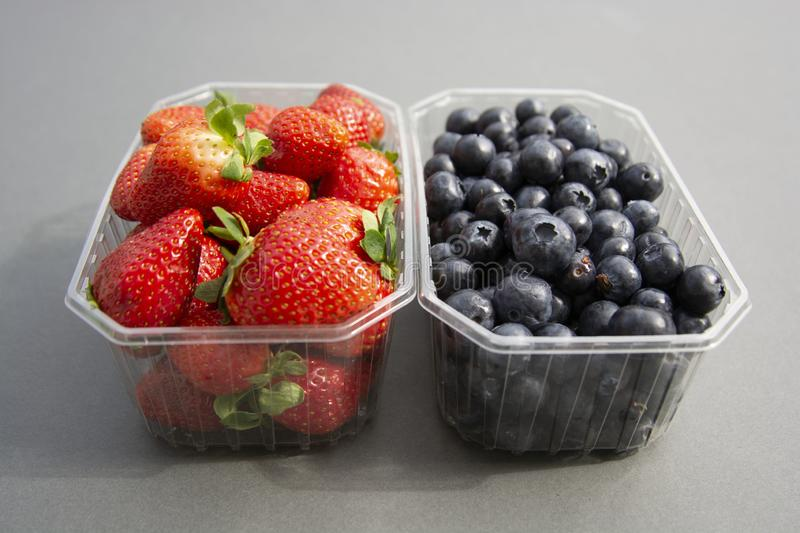 Berries in a plastic container. Fresh strawberry and blueberry in plastic box, isoalted on grey background. Natural sun light royalty free stock photography