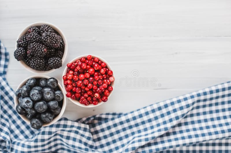 Berries platter with fresh organic red cowberry, blueberry and blackberry wooden table, top view stock photography