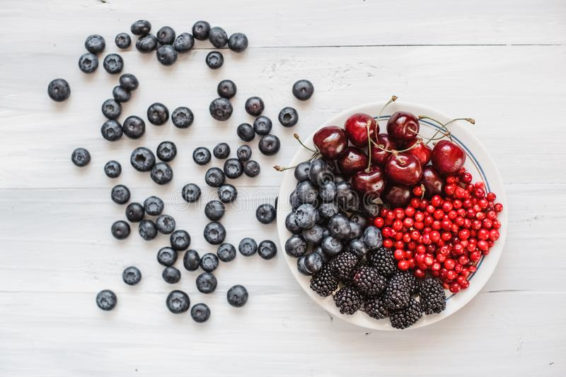 Berries platter with fresh organic red cowberry, blueberry, cherries and blackberry wooden table, top view royalty free stock photos