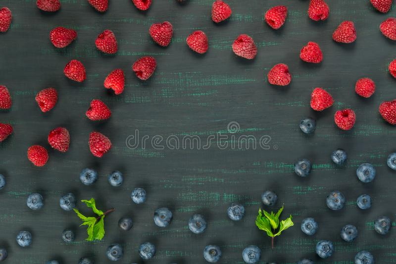 Berries raspberries and blueberries lie on a black background in the middle place for inscription stock photo