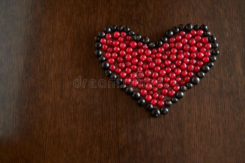 The berries of red currant in the frame of black currant berries are laid out in the form of a heart on a wooden dark background. royalty free stock images