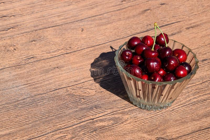 Berries of a sweet cherry in a glass bowl on a wooden background. Ripe red sweet stock photo
