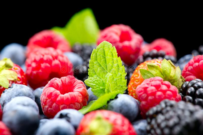 Berries. Various colorful berries background. Strawberry, raspberry, blackberry, blueberry closeup over black. Healthy eating royalty free stock photo