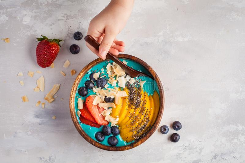 Berry blue smoothie bowl with mango and coconut, top view, copy. Berry smoothie bowl with mango and coconut, top view, copy space. Vegan Healthy Food Concept stock images