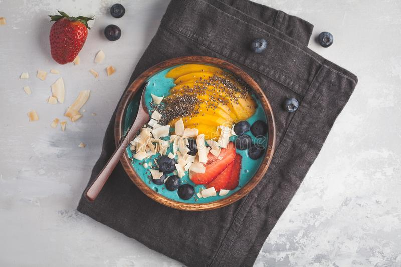 Berry blue smoothie bowl with mango and coconut, top view, copy. Berry smoothie bowl with mango and coconut, top view, copy space. Vegan Healthy Food Concept stock photo