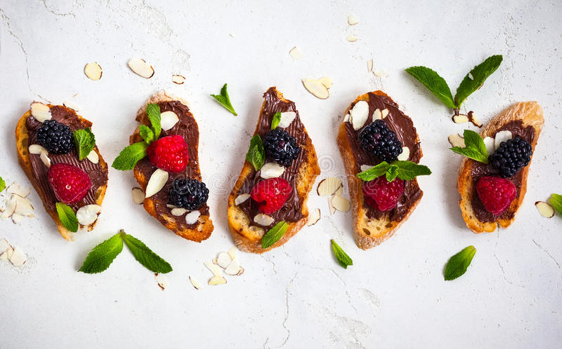 Berry bruschetta. Sweet berry bruschetta with chocolate nut butter,mint and sliced almonds on the white vintage background stock photography