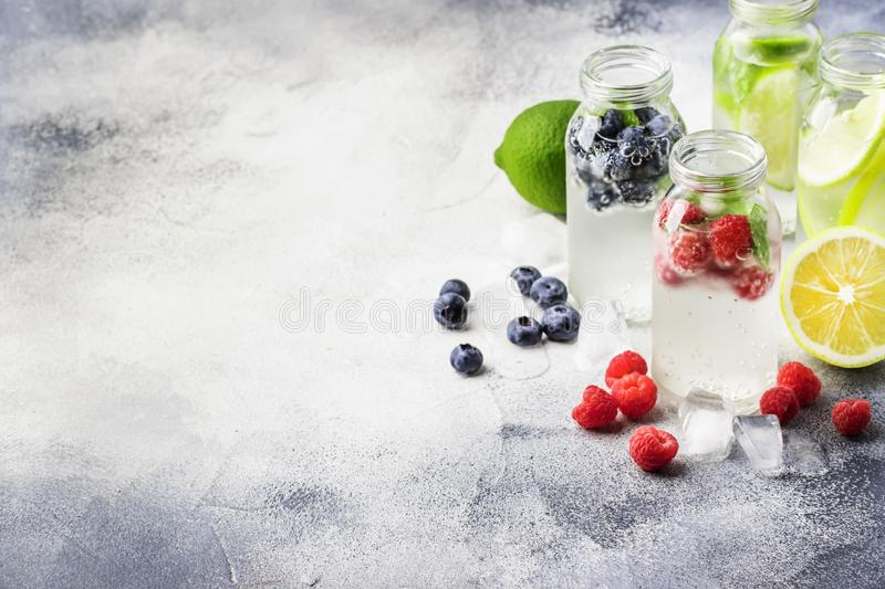 Berry and citrus soft drinks and cocktails in glass bottles on gray stone table background, copy space stock image