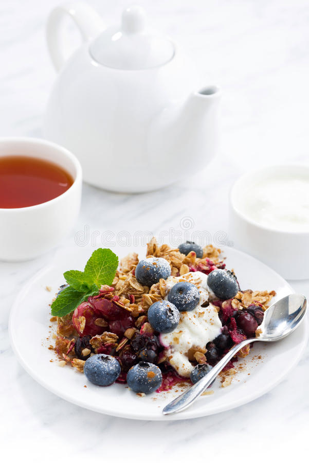 Berry crumble with oat flakes, cream and blueberries, vertical stock photo