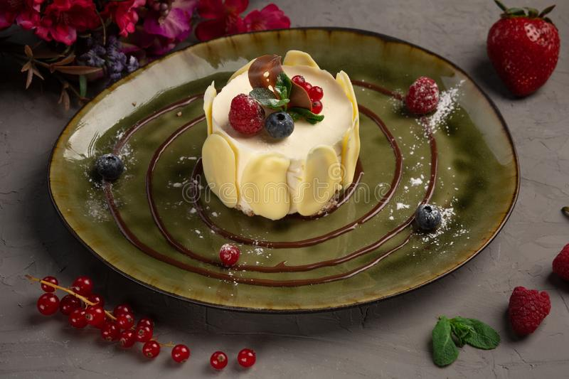 Berry dessert with cream and almond petals. Dessert with cream and almond petals in a green plate on a gray background stock images