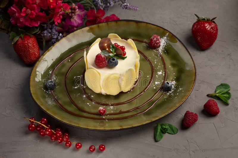 Berry dessert with cream and almond petals. Dessert with cream and almond petals in a green plate on a gray background royalty free stock photos