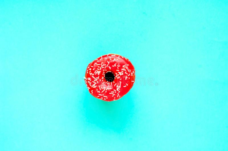 Berry donut with colorful sprinkles on mint background. Concept colorful breakfast. Copy space. Close-up royalty free stock photos