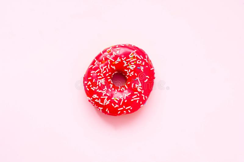 Berry donut with colorful sprinkles on pink background. Concept colorful breakfast. Copy space. Close-up royalty free stock images