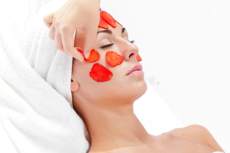 Berry face. Portrait of young beautiful woman being treated royalty free stock images