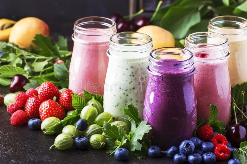 Berry fruit cokctalis, smoothies and milkshakes, fresh fruit and berries on brown table, still life, selective focus royalty free stock photos