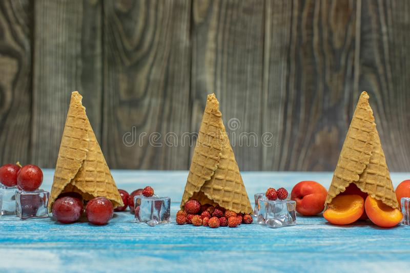 Berry and fruit ice cream. Apricot, strawberry, grape in a waffle cone. Berry and fruit ice cream. Flat lay various fresh fruits apricot, strawberry, grape in a stock photos