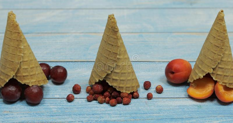 Berry and fruit ice cream. Apricot, strawberry, grape in a waffle cone. Berry and fruit ice cream. Flat lay various fresh fruits apricot, strawberry, grape in a stock image