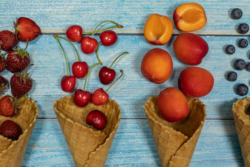 Berry and fruit ice cream. Blueberry, strawberry, cherry, apricot in a waffle. Berry and fruit ice cream. Flat lay various fresh fruits blueberry, strawberry stock image