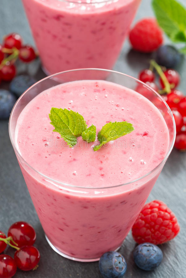 Berry milkshake in glass, top view, vertical stock photo