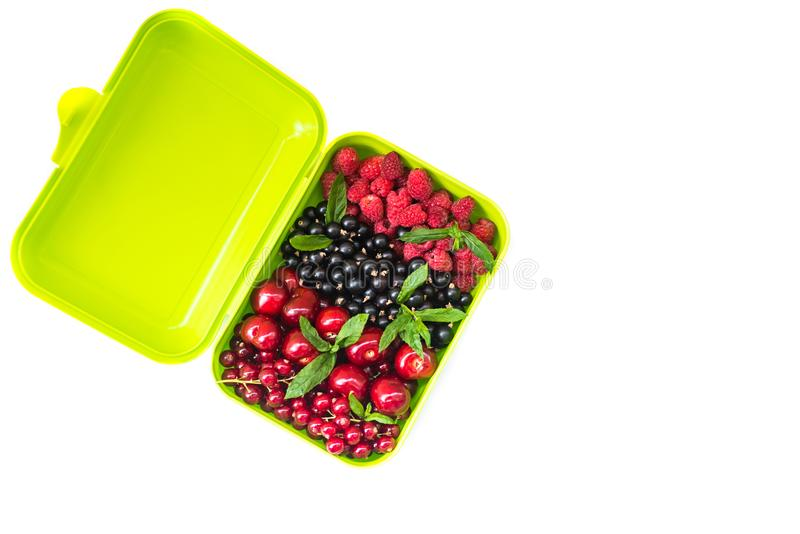 Berry mix: cherry, red and black currant, raspberry in a light green container. royalty free stock image