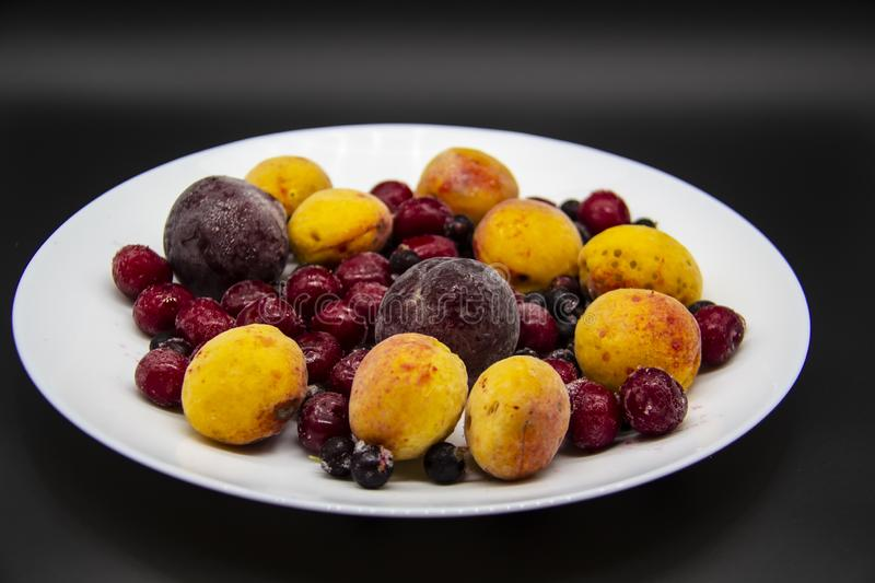 A Berry mix from frozen currant, apricot, plum, cherry. A Frozen Berries from freezer. A sweet background with frozen plum, stock photography