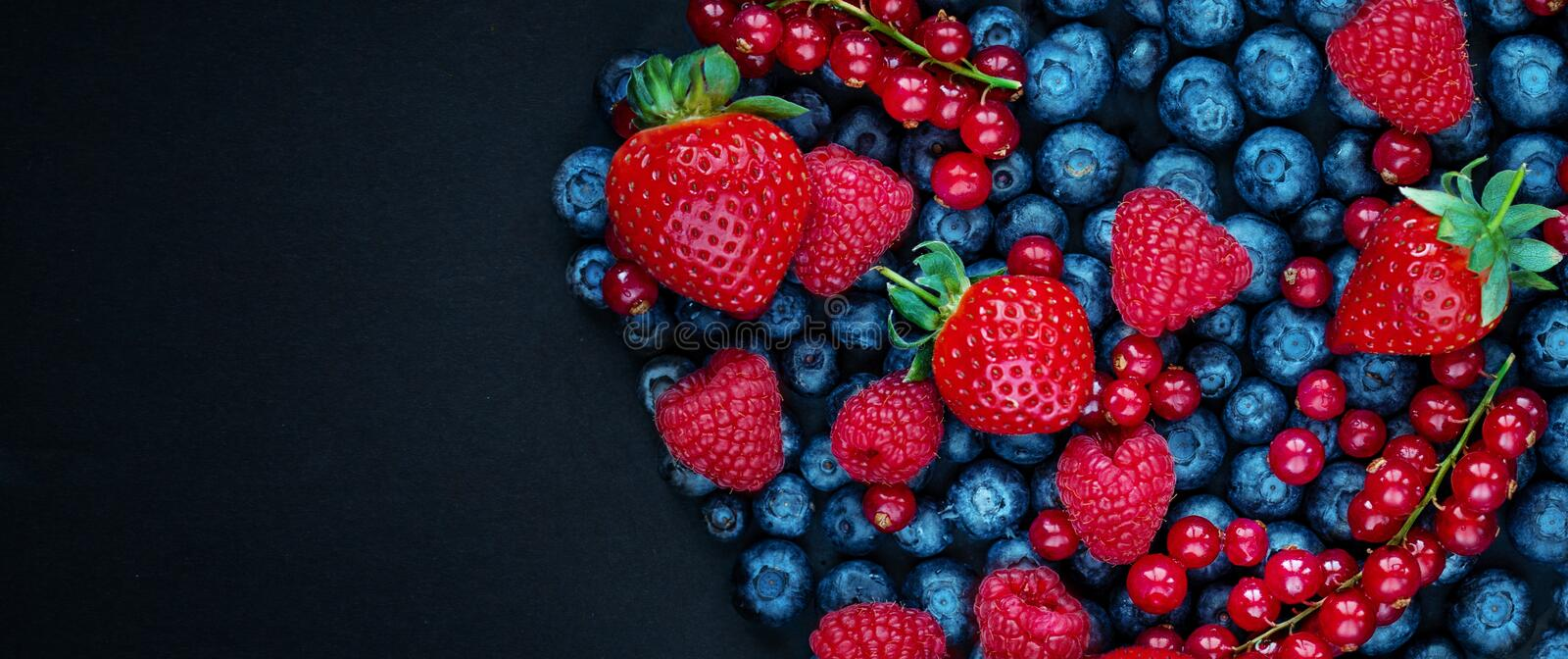 Berry mix isolated on black concrete background. Copy space. Various fresh berries with mint  leaf. Raspberry, Blueberry, stock image