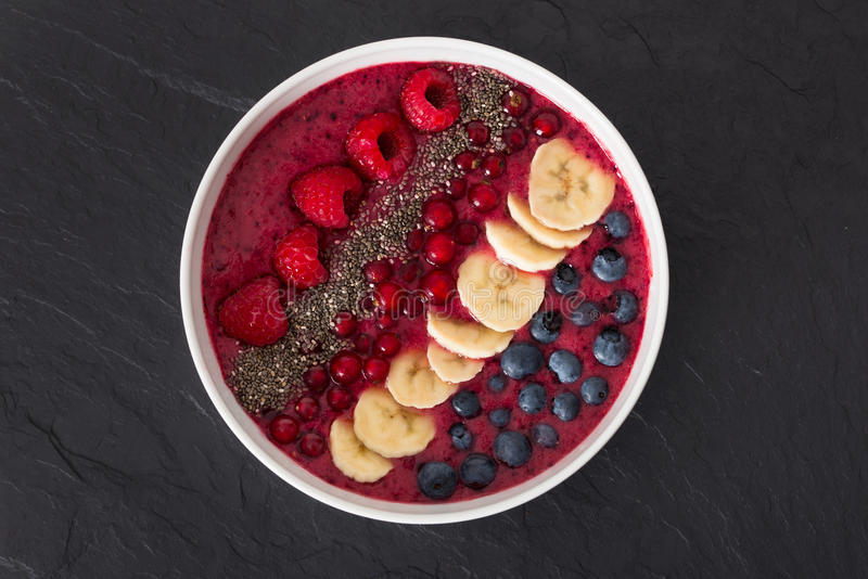Berry smoothie bowl with chia seeds, bananas, blueberries, currant and raspberries on black slate background royalty free stock images