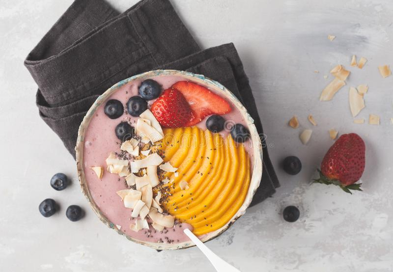 Berry smoothie bowl with mango and coconut, top view, copy space.  royalty free stock photo