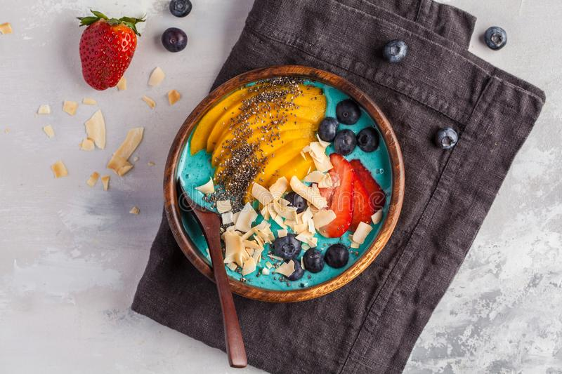 Berry smoothie bowl with mango and coconut, top view, copy space. Berry smoothie bowl with mango and coconut, top view. Vegan Healthy Food Concept stock photo