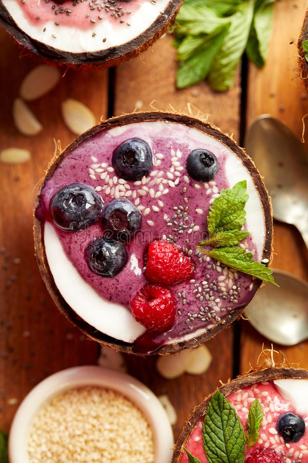 Berry smoothie in a coconut bowl with fresh blueberries and raspberries, mint, almond flakes, chia seeds and sesame seeds. Health stock photos