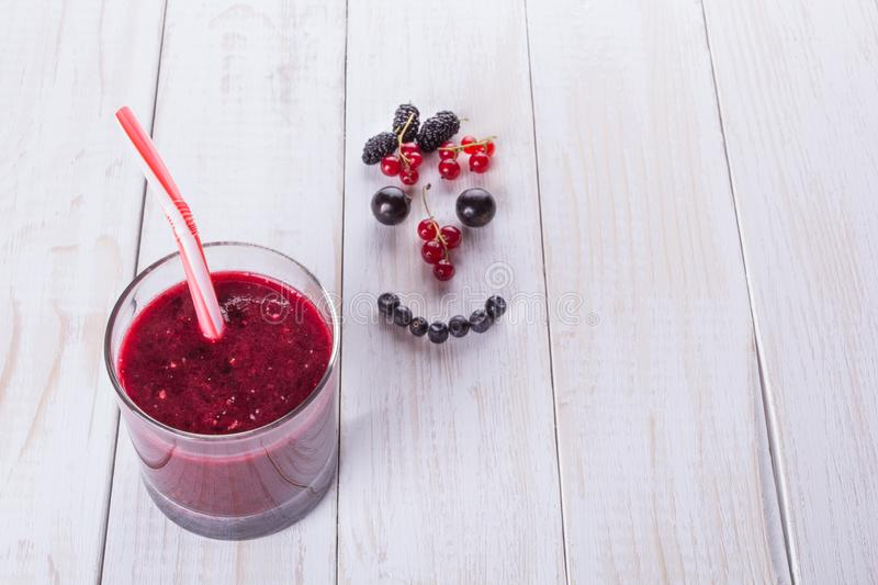 Berry smoothie in a glass jar with a straw, over vintage wood table with fresh mulberry berries, blackberries and currants. Smile stock photo
