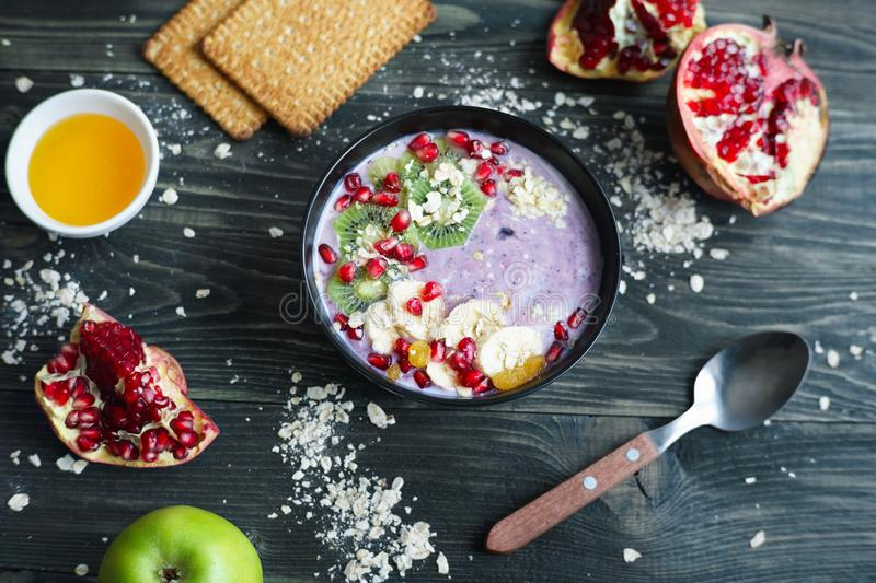 Berry yoghurt smoothie bowl with kiwi and banana slices, raisins. And pomegranate. Healthy diet meal for breakfast royalty free stock images