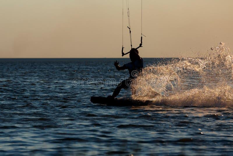 Berufs-kiter, das einen schwierigen Trick auf einem schönen Sonnenunterganghintergrund tut lizenzfreie stockfotos