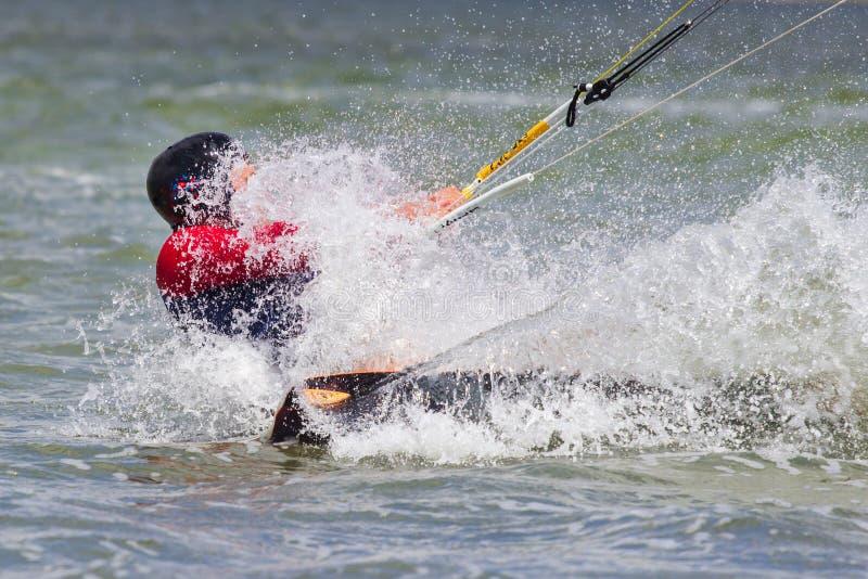 Berufs-kiter macht den schwierigen Trick auf einem schönen Hintergrund des Sprays stockfotografie
