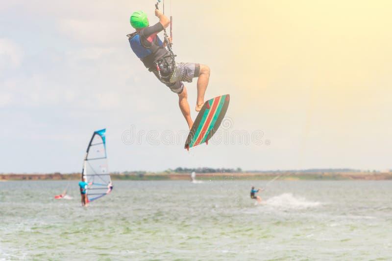 Berufs-kiter macht den schwierigen Trick auf einem schönen Hintergrund am sonnigen Tag lizenzfreie stockfotografie