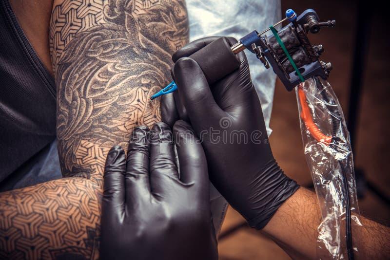 Berufs-tattooer, das Prozess der Herstellung einer Tätowierung im tatt zeigt stockbild