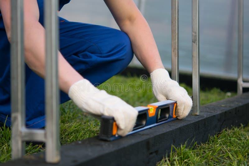 Berufsarbeitskraft überprüft unter Verwendung eines Niveaus, ein sogar Oberflächen der Grundlage des Gewächshauses lizenzfreie stockfotografie