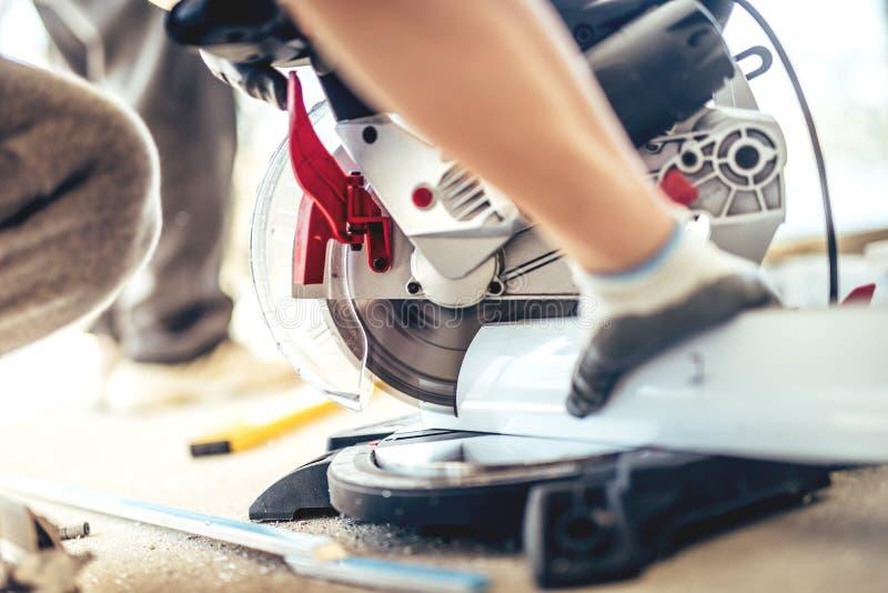 Berufsarbeitskraft, die eine Gehrungsfugesäge und einen Winkelschleifer für den Schnitt des Metalls und des Aluminiums verwendet stockfoto