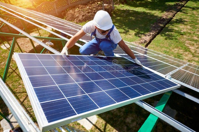 Berufsarbeitskraft, die Sonnenkollektoren auf den grünen Metallbau installiert lizenzfreie stockbilder