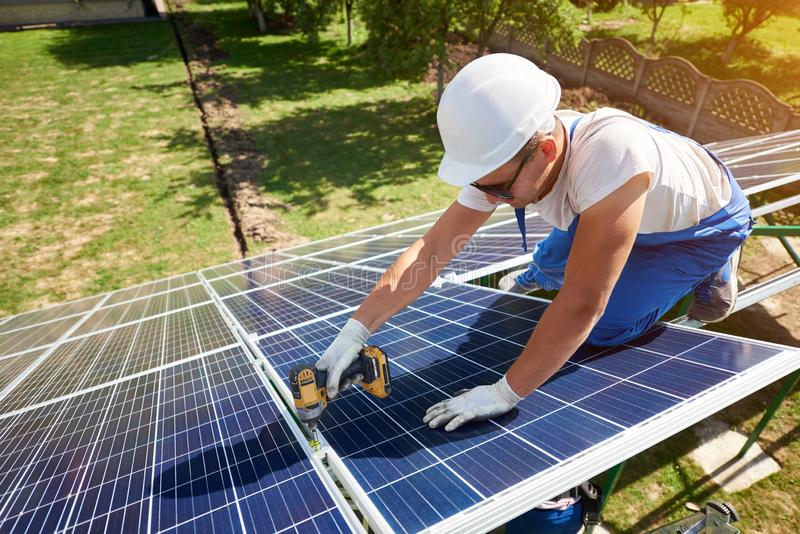 Berufsarbeitskraft, die Sonnenkollektoren auf den gr?nen Metallbau installiert stockfotografie