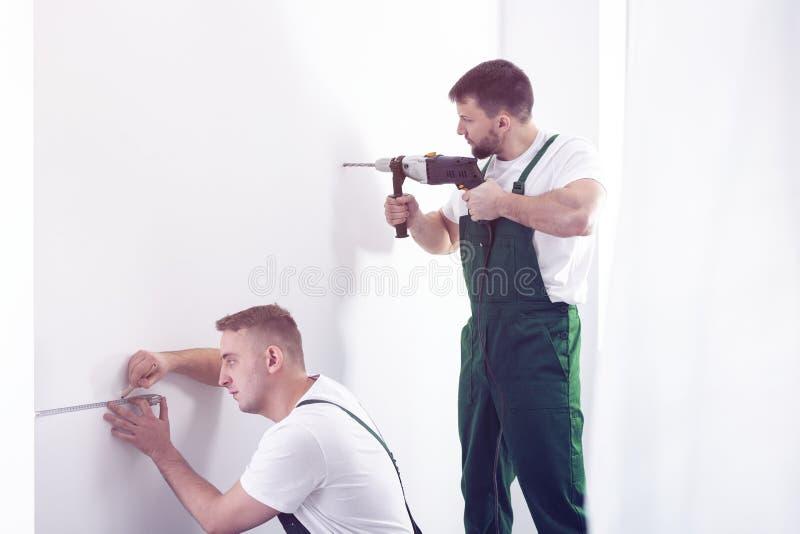 Berufsauftragnehmerbohrung in einer weißen Wand mit einem Werkzeug und lizenzfreie stockfotos