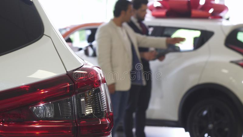 Berufsautoverkäufer, der Autos für Verkauf zu seinem männlichen Kunden zeigt lizenzfreies stockfoto