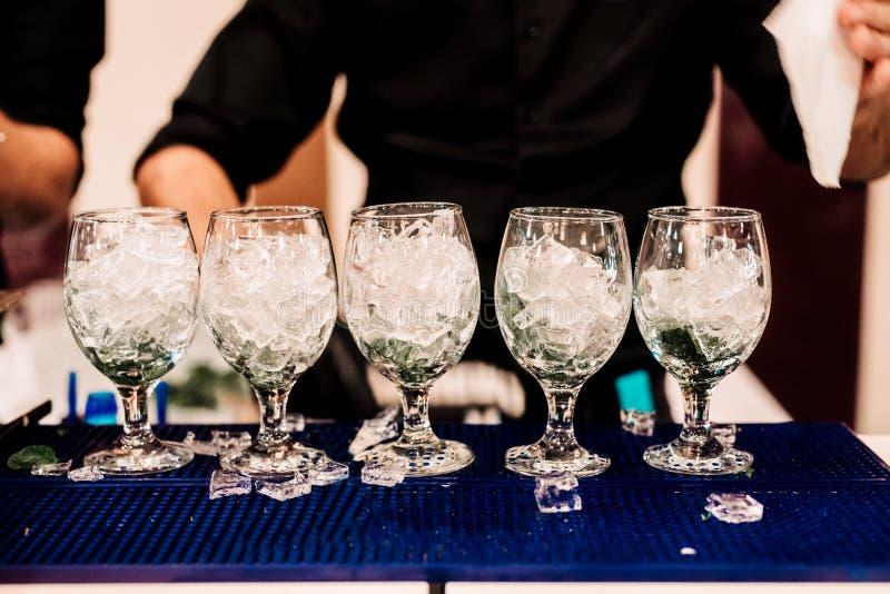 Berufsbarmixer, der einige Cocktails, alkoholische Getränke mit Minze, Eis und Rum zubereitet Mojito trinkt bereites gedient zu w stockfotografie
