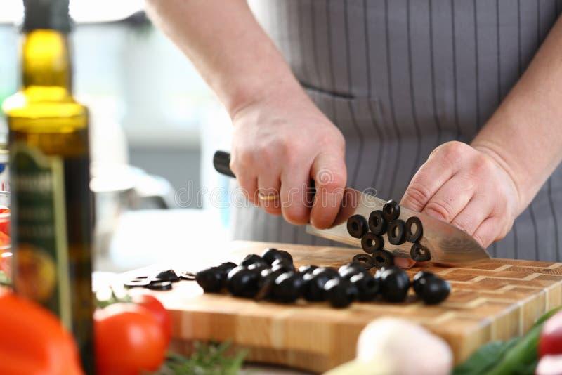 Berufschef Cutting Black Olive Ingredient lizenzfreie stockfotografie
