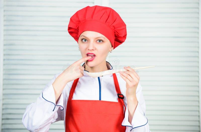 Berufschef in der K?che cuisine Frau im Kochhut und -schutzblech glückliche Frau, die gesunde Nahrung durch Rezept kocht lizenzfreie stockfotos