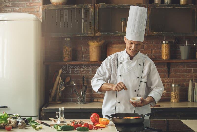 Berufschef des reifen Mannes, der zuhause Mahlzeit kocht lizenzfreie stockbilder