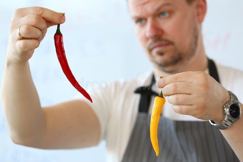 Berufschef Showing Yellow Chili Pepper lizenzfreie stockbilder