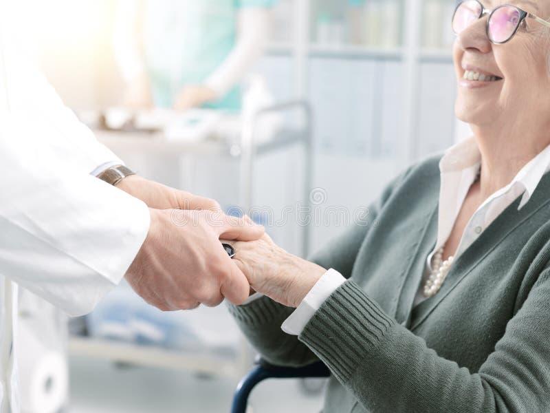 Berufsdoktor, der die Hände eines älteren Patienten hält lizenzfreies stockfoto