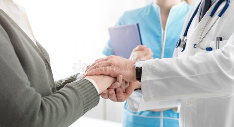 Berufsdoktor, der die Hände eines älteren Patienten hält stockfoto