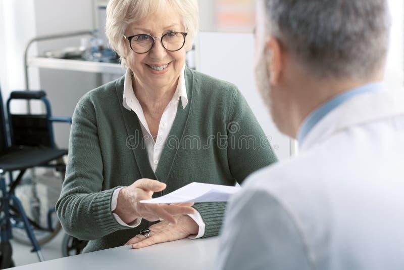 Berufsdoktor, der einem älteren Patienten eine Verordnung gibt lizenzfreies stockfoto
